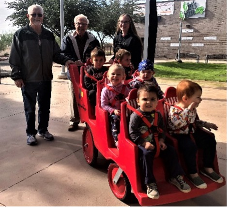 Older adults accompany children and staff on their buggy walk at Benevilla.